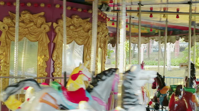 Amusement park. Carousel with horses. Children and adults ride and enjoy