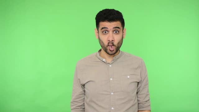 Amusing funny brunette man making fish face with big eyes grimace, green background, chroma key