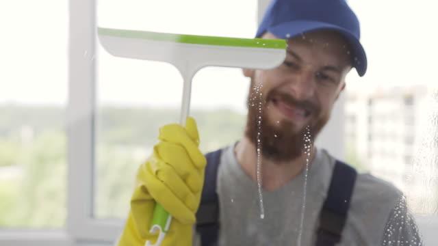 vidéos et rushes de nettoyeur barbu mâle amusant dans l'uniforme bleu lavant la fenêtre avec le jet de nettoyant et le squeegee spécial - raclette