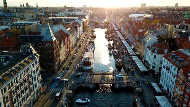 amzing backlight sunset footage from copenhagen, denmark. bridge in nyhavn new harbour canal and entertainment district. aerial video footage view from the top. forward movement. sunset golden light - копенгаген стоковые видео и кадры b-roll