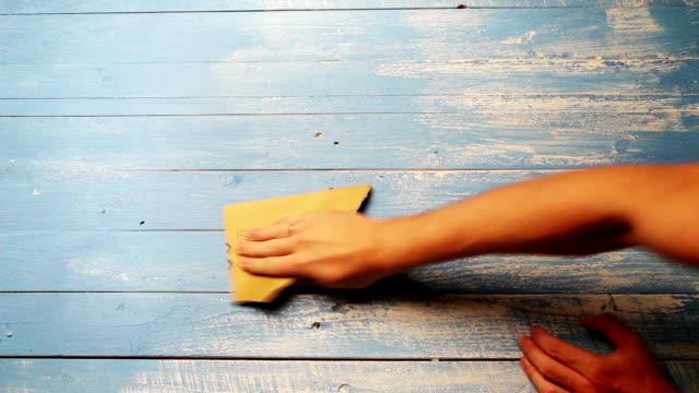 Un rapide polissage plans-séquences d'une personne à la planche de bois avec papier de verre pour pouvoir look plus - Vidéo