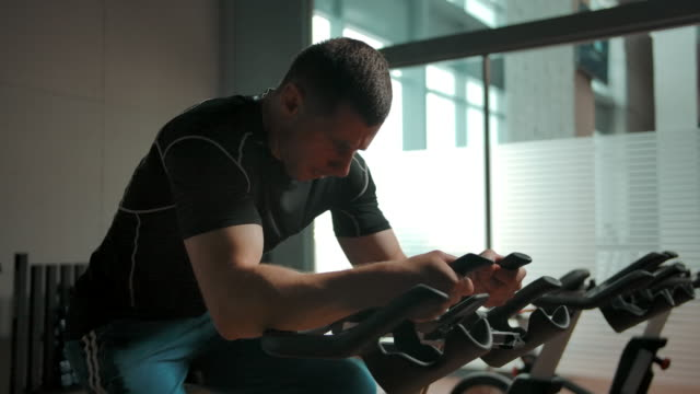 An active male athlete pedals on a stationary bike in a sports hall An active male athlete pedals on a stationary bike in a sports hall. Power loads on the feet of the concept. It's a hard exercise. Slow motion. exercise bike stock videos & royalty-free footage