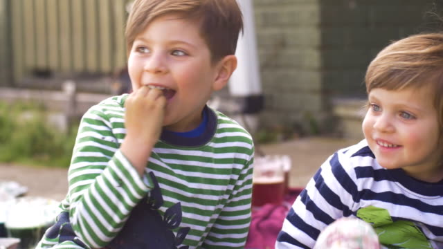 An adorable happy young girl and boy sitting outside smiling together video