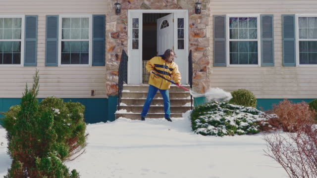 An adult 50-years-old long-haired man wearing a yellow jacket cleaning the porch, stairs and path in the front yard of the country house from the snow after a winter snowfall. Poconos, Pennsylvania, USA