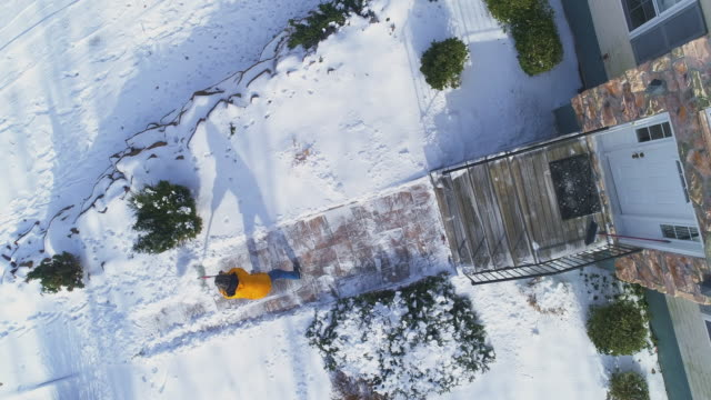 An adult 50-years-old long-haired man wearing a yellow jacket cleans snow with a shovel the path in the front yard of the country house after a winter snowfall.