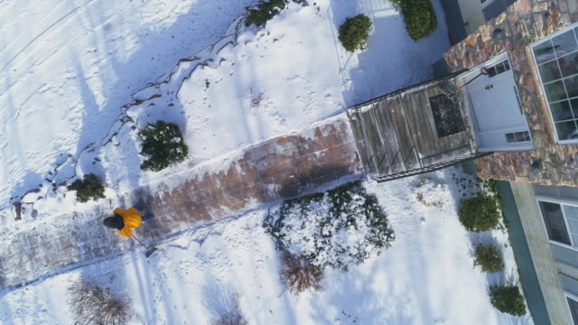 An adult 50-years-old long-haired man wearing a yellow jacket sweeps the path, sweeping away snow in the front yard of the country house from the snow after a winter snowfall.