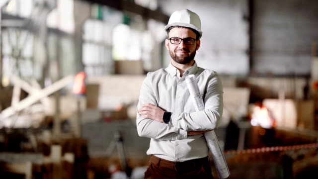 An adult architect in a helmet stands at the current construction site, in his hands a project for the modernization of an abandoned factory in the city видео