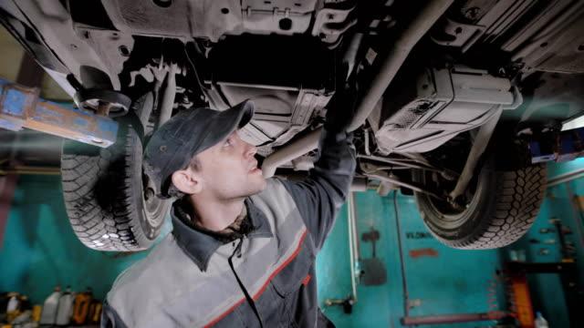 成人男性がタイヤ サービス店で車両の状態をチェック、労働者はマシンの状態をチェック ビデオ