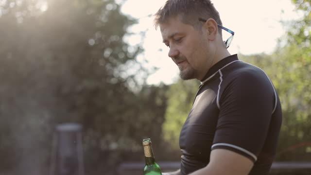 vídeos y material grabado en eventos de stock de un hombre adulto bebe cerveza al aire libre y cocina carne a la parrilla. de humo. - pinzas utensilio para servir