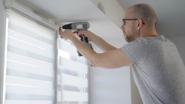 yetişkin bir adam bir elektrikli matkap elinde tutar ve onu ışıktan korur pencere vidalar - ayarlamak stok videoları ve detay görüntü çekimi
