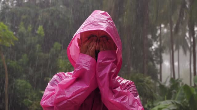 An adult man in a pink raincoat enjoys the tropical rain. Slow motion