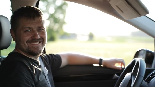 An adult man with a beard is sitting in the car and smiling.