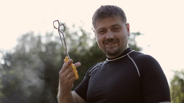 vídeos y material grabado en eventos de stock de un hombre adulto con barba convierte caliente filetes en la parrilla. - pinzas utensilio para servir