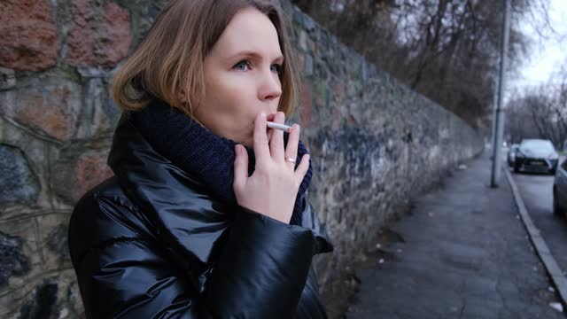 An adult woman lights a cigarette and blows smoke in the street.