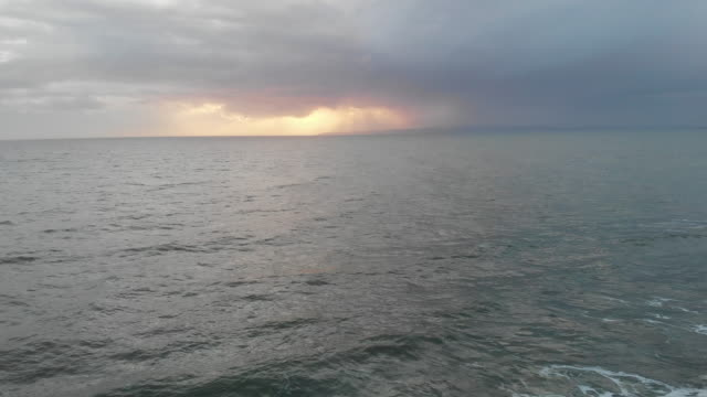 An aerial backward footage of crashing waves on a choppy sea under a stormy grey sky with sun glowing behind clouds