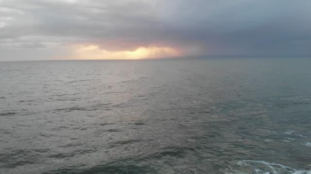 stockvideo's en b-roll-footage met een achteruit beeld van een luchtfoto van beukende golven op een schokkerige zee onder een stormachtige grijze hemel met zon gloeiend achter wolken - bewolkt