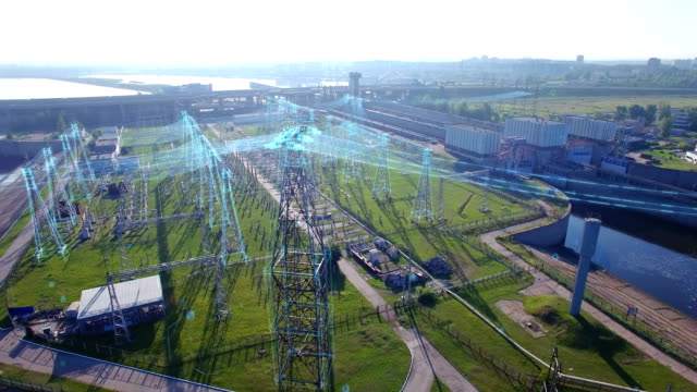 an aerial circular orbit view, high voltage electric power tower with infographic power flows, hydroelectric power station and electric substation with tall pylons and hog voltage distribution cables. - sottostazione elettrica video stock e b–roll
