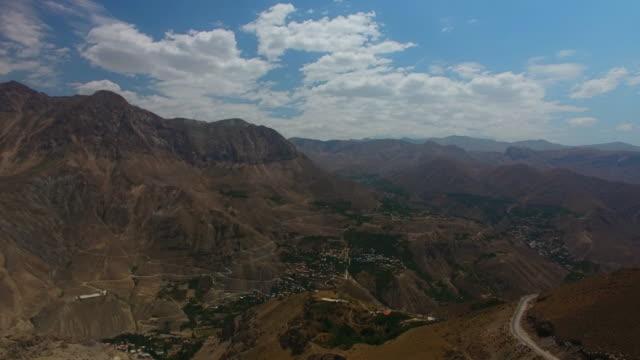 bulutlu gün altında dağların ve vadinin muhteşem manzarasinda bir hava çekimi - mountain top stok videoları ve detay görüntü çekimi