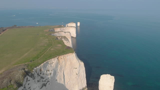 An aerial sideway (Left to right) footage of the Old Harry Rocks with crystal blue water along beautiful white cliffs under an amazing hazing blue sky An aerial sideway (Left to right) footage of the Old Harry Rocks with crystal blue water along beautiful white cliffs under an amazing hazing blue sky heat haze stock videos & royalty-free footage