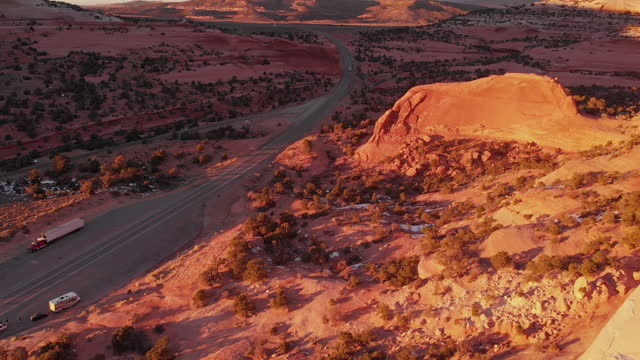 An Aerial Sunset View Of Wilson Arch, Near Moab, Utah, With Semi Trucks Driving The Major Truck Route Delivering Freight