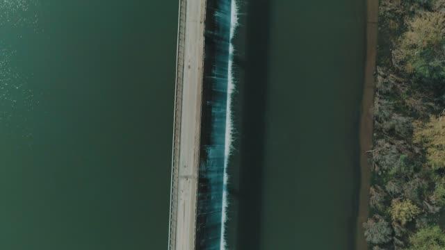 an aerial vertical 'bird's eye view' shot of a road over a dam video