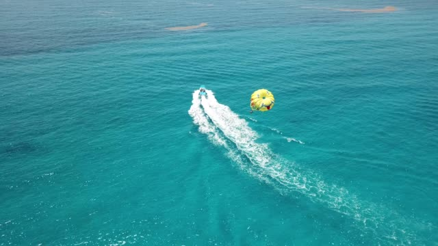An aerial view of parasailing at a Cancun beach on a perfect day Parasailing at Playa Delfines a popular beach in Cancun, Mexico's Hotel Zone from an aerial view beach party stock videos & royalty-free footage