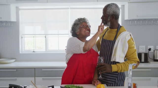 An african american couple spending time together in the kitchen social distancing in quarantine.