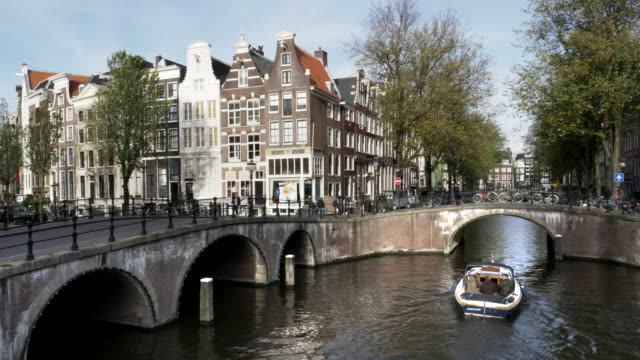 an afternoon wide view of dutch buildings, canals and bridges in amsterdam - canale video stock e b–roll