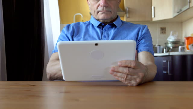 An aged male  sits and uses a tablet PC at home (dolly) video
