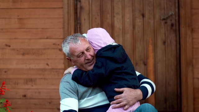 An ageing man is having great time with his grandchildren. He hugs them, they run into his embrace. Slow mo video