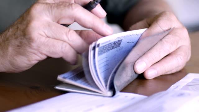 an aging senior balances his checkbook - fraud stock videos & royalty-free footage