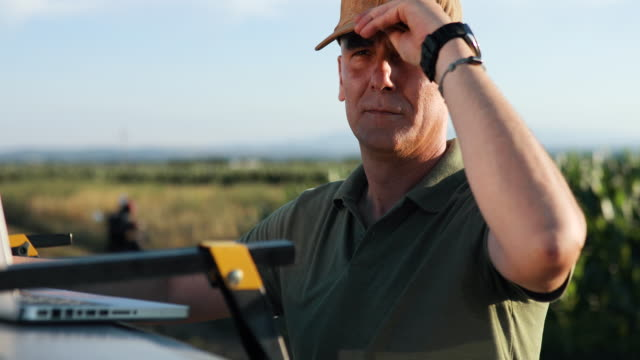 An agronomist at work. It prints a report on its laptop. He puts a cap on his head video