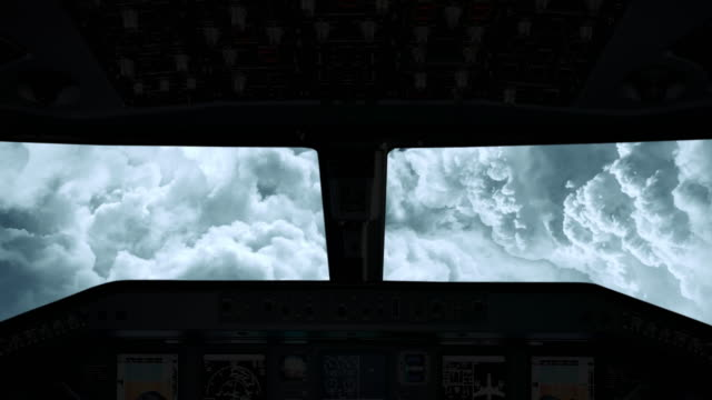 An airplane cockpit view flying straight through the clouds