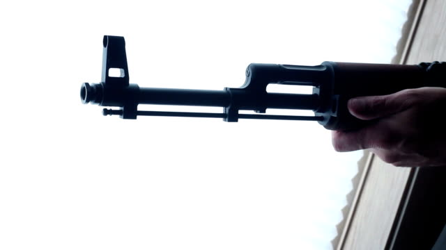 An AK-47 Kalashnikov assault rifle is raised in ambient home setting video