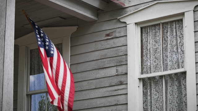 an american flag waves on a farmhouse porch - american flag стоковые видео и кадры b-roll