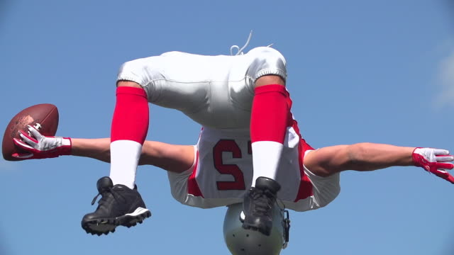 An American Footballer backflips and Celebrates. An American Footballer celebrates with a backflip and throws the ball away in excitement. touchdown stock videos & royalty-free footage