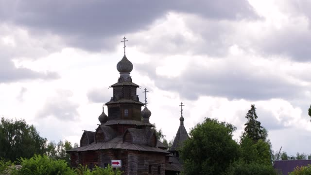 an ancient wooden temple stands in dense greenery. - lingua russa video stock e b–roll