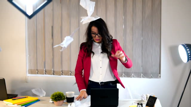 An angry business woman throws papers in the office