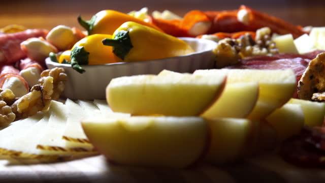 закуска charcuterie мясо / сырная доска с различными мясом, сырами и крекерами на столе в помещении празднование / партия - закуска стоковые видео и кадры b-roll