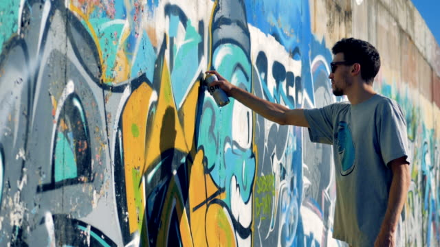 An artist adds some paint to a finished graffiti. video