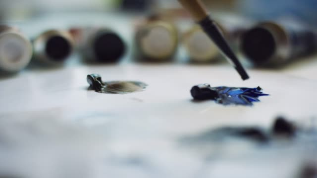an artist dips a small paintbrush into blue oil paint on a palette - tavolozza video stock e b–roll