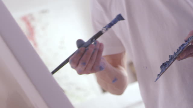 an artist is painting a picture - cavalletto attrezzatura per arti e mestieri video stock e b–roll