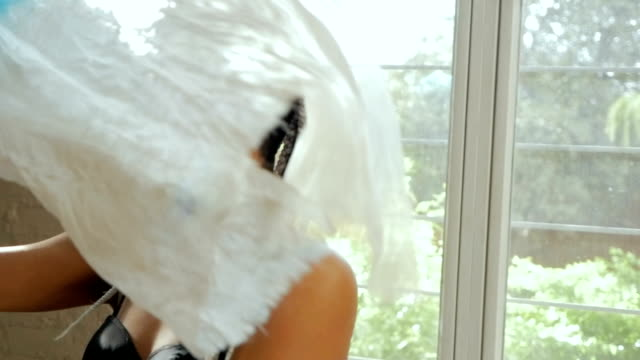 An artistic young woman dancing with flowing fabric in slowmo video