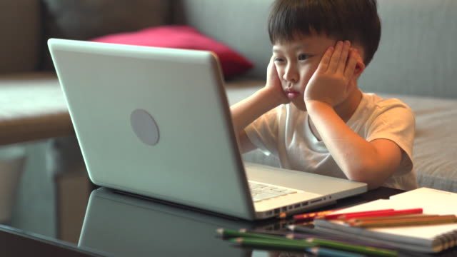 An Asian boy pretended to be bored while studying. online. People are bored with having to stay home, detained during the COVID-19 virus epidemic.