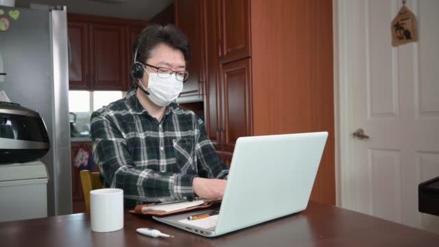 アジアのビジネスマンは、大規模なパンデミックのために自己孤立し、自宅で働いています。 - オペレーター 日本人点の映像素材/bロール