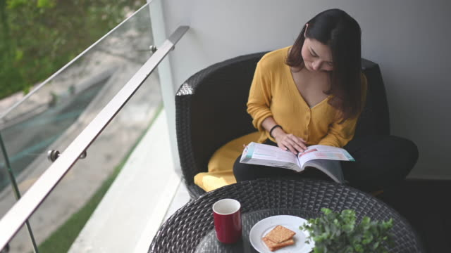 an asian chinese beautiful woman reading book in her balcony during noon relaxing and enjoying her digital detox me-time with coffee and biscuit for snack