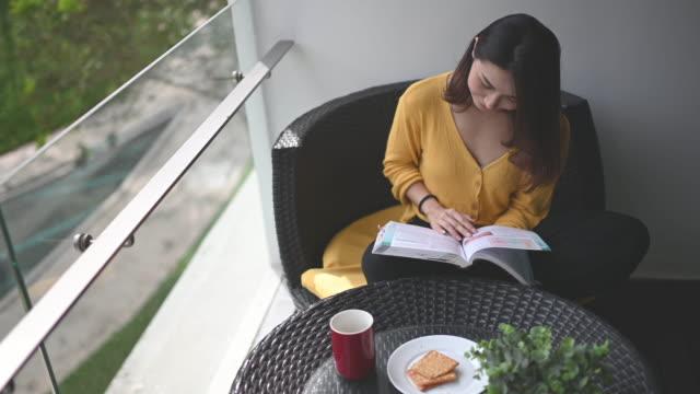 vídeos de stock, filmes e b-roll de uma mulher asiática chinesa linda lendo livro em sua varanda durante o meio-dia relaxando e desfrutando de seu digital desintoxicação me-time com café e biscoito para lanche - hobbie