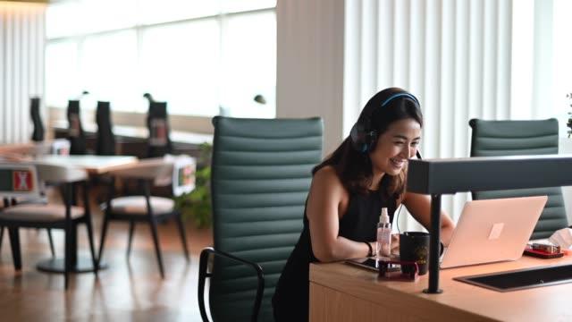 stockvideo's en b-roll-footage met een aziatische chinese mooie vrouwen witte boordenarbeider die aan de video die videoconferentie van de camera roept met zijn bedrijfspartners met gezichtsmasker spreekt - aziatische etniciteit