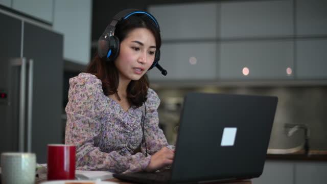 una bella donna cinese asiatica che lavora da casa come servizio clienti rispondendo al suo cliente online usando laptop e cuffie in cucina digitando - commercio elettronico video stock e b–roll