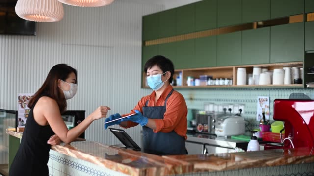 an asian chinese cafe owner businesswoman taking order from her customer at counter using digital tablet - new normal video stock e b–roll